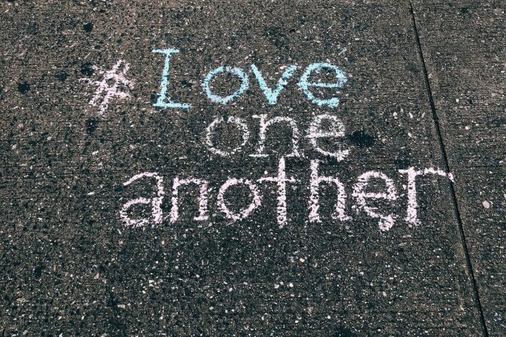 Love one another written in chalk on sidewalk