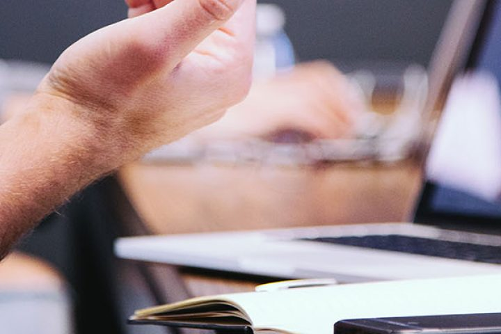 Person's hands gesturing during meeting